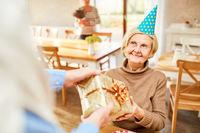 Seniorin freut sich über ein Geburtstagsgeschenk