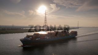 Containerschiff auf der Elbe in Fahrt bei Sonnenuntergang
