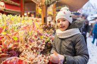 girl with lollipop at christmas market candy shop