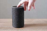 hand turning off smart speaker microphone