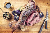 Marinated barbecue aged leg of venison with mushrooms and red cabbage as top view on a rustic board