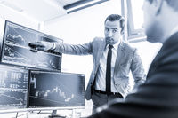Stock brokers trading online in corporate office.