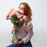 Sexy girl with a bouquet of delicate pink roses in a transparent vase on a gray background with copy space. St. Valentine's Day