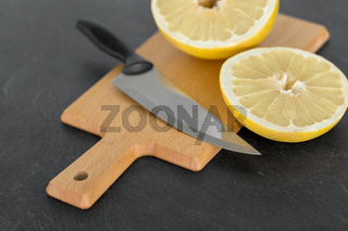 close up of lemon and knife on cutting board