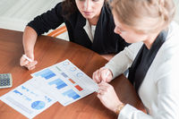 Business women pointing at diagrams