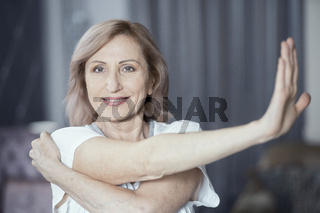 Charming woman is stretching hands before doing yoga exercise