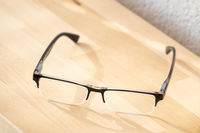 reading glasses on a wooden table