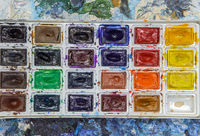Old watercolor paint on a palette. Concept of art and creativity.
