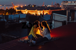 Loving couple is sitting on the roof of the house.