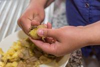 Köchin schält frisch gekochte Kartoffeln - Nahaufnahme