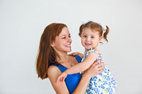 Young woman having fun with daughter indoors