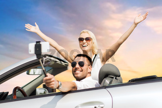 couple in car taking selfie by smartphone over sky