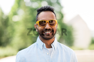 happy young indian man in sunglasses outdoors