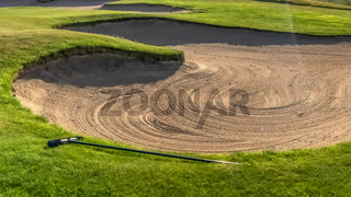 Panorama Sand bunker of a golf course and view of bright sun and puffy clouds in the sky