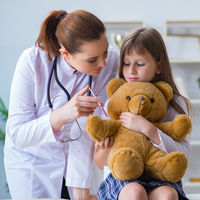 Woman female doctor examining little cute girl with toy bear