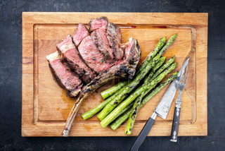 Barbecue dry aged wagyu tomahawk steak with green asparagus as top view on a wooden board