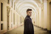Handsome young man under cloisters in Italian city at night