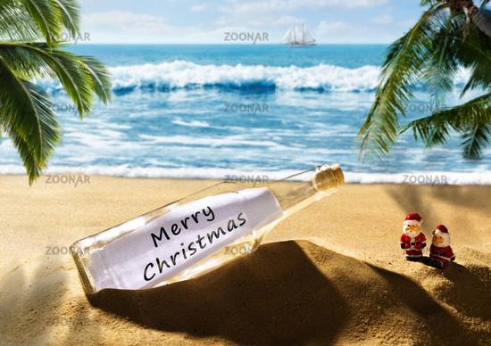 Flaschenpost mit der Nachricht Merry Christmas am Strand