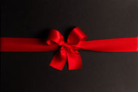 Red gift bow on black