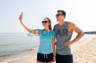 couple taking selfie by smartphone on beach