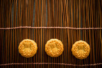 Mooncakes on bamboo mat with copy space dark light