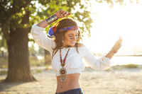 Happy slim tan woman in jeans dancing on the beach