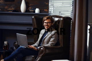 Smiling happy young man sitting in co-working office room