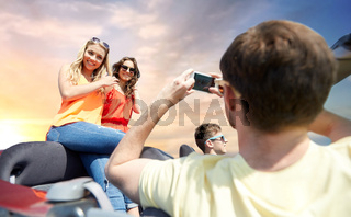 friends photographing in convertible car