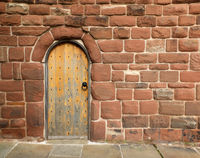 an ancient brown wooden door in a red sandstone medieval wall