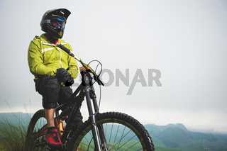 Portrait of a man aged on a mountain bike in the mountains in cloudy weather. Mountain bike concept