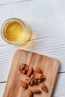 A jar with fresh honey and almonds on a kitchen board on a white wooden table.Top view