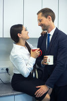Happy couple of young business people having coffee in office