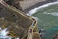 Besucher überqueren die  steinerne Brücke zur Insel Gaztelugatxe bei Bakio, Baskenland, Spanien