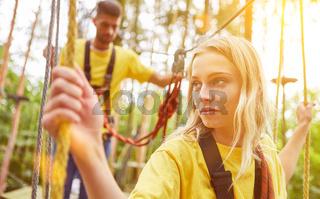 Frau lernt Klettern im Hochseilgarten oder Kletterwald