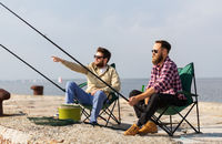 male friends with fishing rods on pier