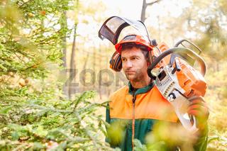 Mann als Forstwirt und Holzfäller in Schutzausrüstung