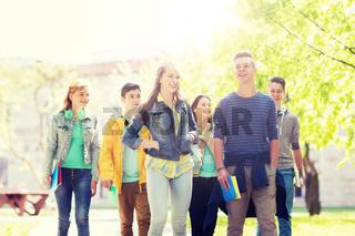 group of happy teenage students walking outdoors