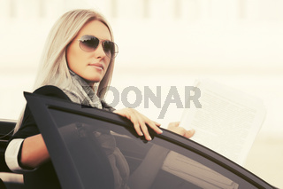 Fashion business woman in sunglasses outside a her car