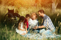 Happy family taking selfie on the picnic in park. Paraplegic