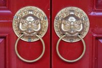 Golden colored chinese door knockers on a red door