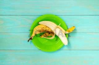 Peeled banana in a green plate