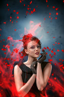 Abstract fashion portrait of young woman with flame and smoke over dark background