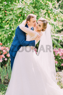 The groom is hugging and kissing the smiling bride. Park location.
