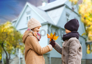 kids with autumn maple leaves over house outdoors