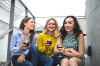 Three young happy woman laughing, drinking red wine, having fun