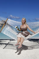 the woman with blonde long hair in  long dress with a rose in a hammock on background of the sea