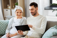old mother and adult son with tablet pc at home