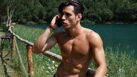Shirtless young man making phone call at lake