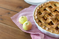 apple pie in baking mold on wooden table