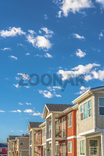 Homes with white and orange exterior wall against cloudy blue sky on a sunny day